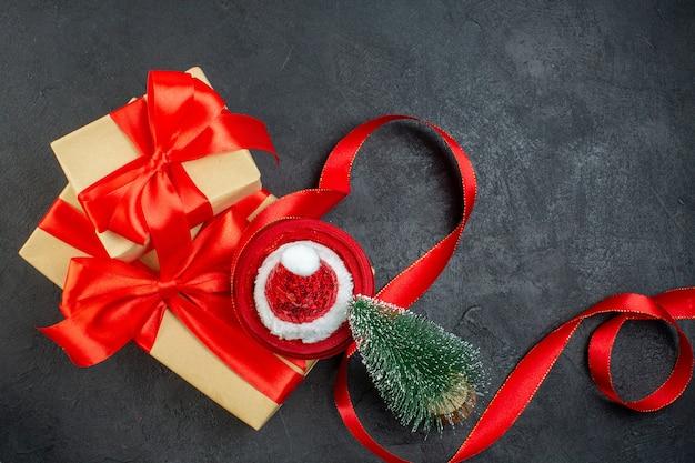 Visão aérea de lindos presentes com fita vermelha e chapéu de papai noel, árvore de natal na mesa escura