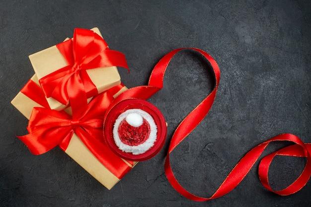 Visão aérea de lindos presentes com fita vermelha e chapéu de papai noel na mesa escura