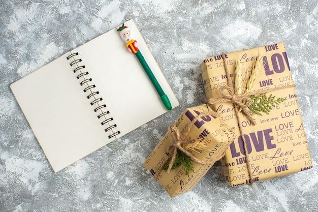 Visão aérea de lindos presentes de natal embalados, grandes e pequenos, e cadernos abertos com uma caneta na mesa de gelo