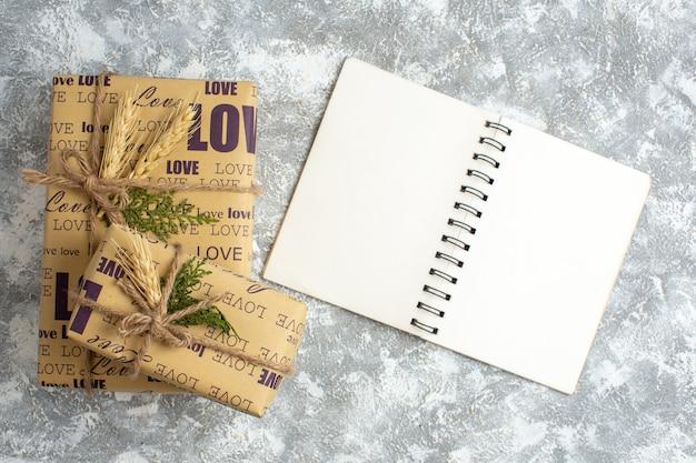 Visão aérea de lindos presentes embalados de natal com inscrição de amor no caderno aberto na mesa de gelo
