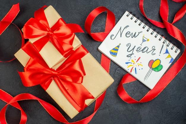 Visão aérea de lindos presentes empilhados com fita vermelha e caderno com escrita de ano novo e desenhos em fundo escuro