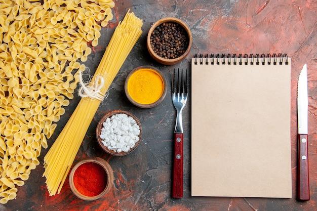 Visão aérea de macarrão cru em várias formas diferentes especiarias e caderno com garfo e faca na mesa preta