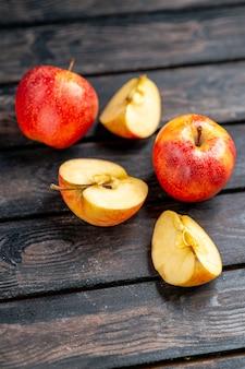 Visão aérea de maçãs frescas naturais picadas e vermelhas inteiras em fundo preto