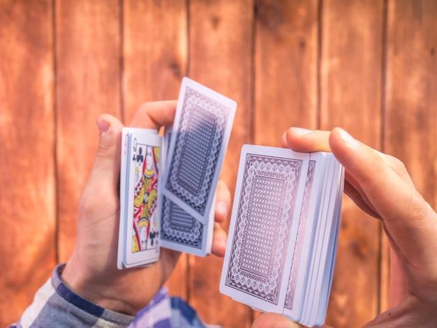 Visão aérea, de, mãos, misturando, cartas de jogar, ligado, a, madeira, superfície