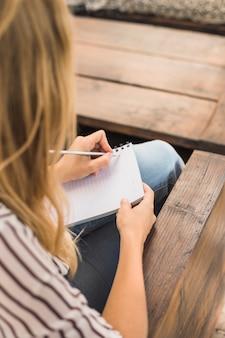Visão aérea, de, mulher jovem, escrita, ligado, caderno, com, lápis