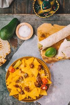 Visão aérea de nachos mexicanos chips de tortilla; limão; abacate no fundo enferrujado