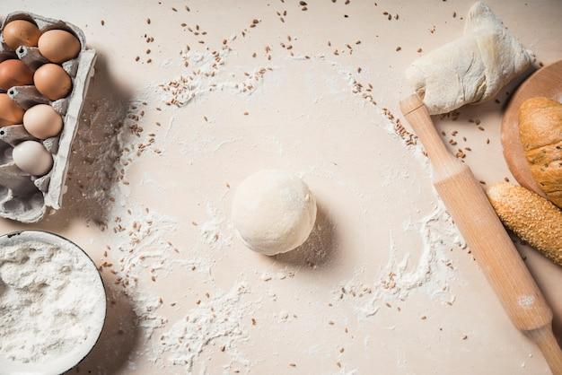 Visão aérea de ovos; farinha; massa e pães assados no fundo
