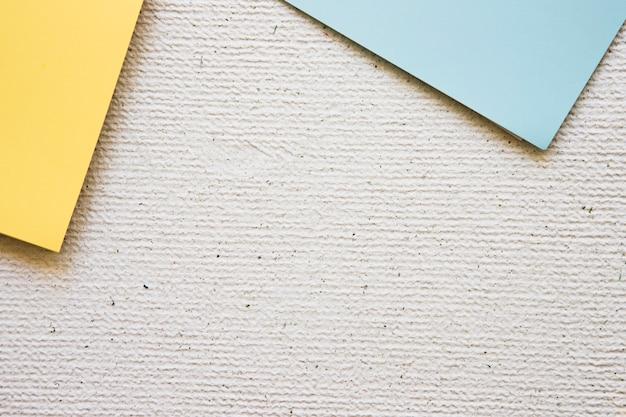 Visão aérea de papéis de cartão cinza e amarelos sobre fundo de concreto