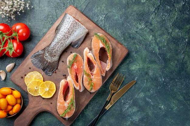 Visão aérea de peixes crus rodelas de limão, verdes, pimenta na tábua de madeira, talheres de tomate na mesa escura