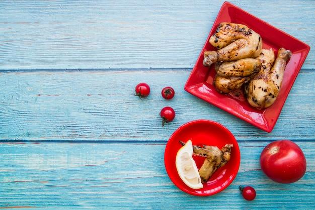 Visão aérea de pernas de frango assado e asas de frango na placa vermelha com tomate e fatia de limão contra a mesa de madeira azul