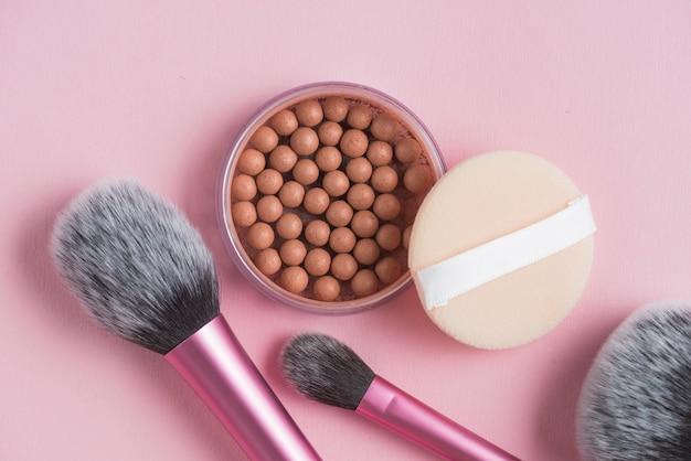 Visão aérea de pérolas bronzeadoras; esponja e maquiagem escovas no pano de fundo rosa