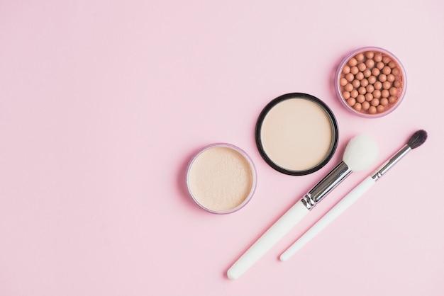 Visão aérea de pós de rosto; bronzeando pérolas e pincéis de maquiagem no pano de fundo rosa
