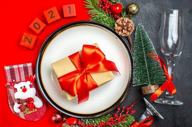 Visão aérea de pratos de jantar acessórios de decoração ramos de abeto xsmas números de meias em um guardanapo vermelho e taça de vidro de árvore de natal em fundo escuro