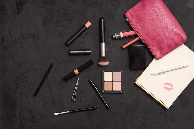 Visão aérea de produtos de maquiagem saindo de uma bolsa de cosméticos rosa em uma superfície preta