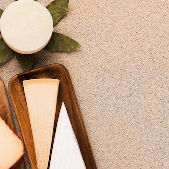 Visão aérea de queijo branco; queijo parmesão e queijo manchego espanhol arranjado sobre o pano de fundo liso