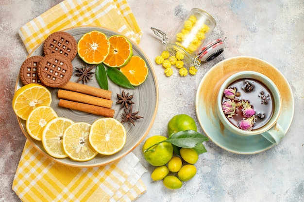 Visão aérea de rodelas de limão, canela e limão em uma tábua de madeira e biscoitos na mesa branca