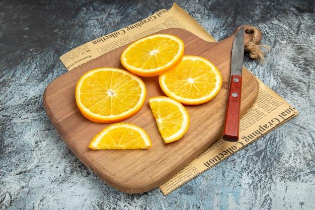 Visão aérea de rodelas de limão fresco com faca na tábua de madeira no jornal sobre fundo cinza