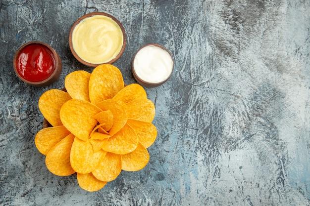 Visão aérea de saborosas batatas fritas decoradas em forma de flor e sal com maionese de ketchup na mesa cinza