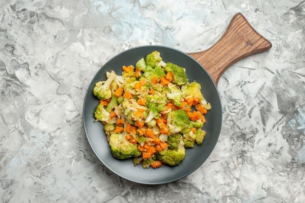 Visão aérea de salada de legumes fresca e saudável em uma tábua de madeira na mesa branca