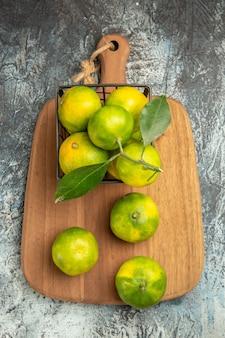 Visão aérea de tangerinas verdes com folhas dentro e fora de uma cesta na tábua de madeira na mesa cinza