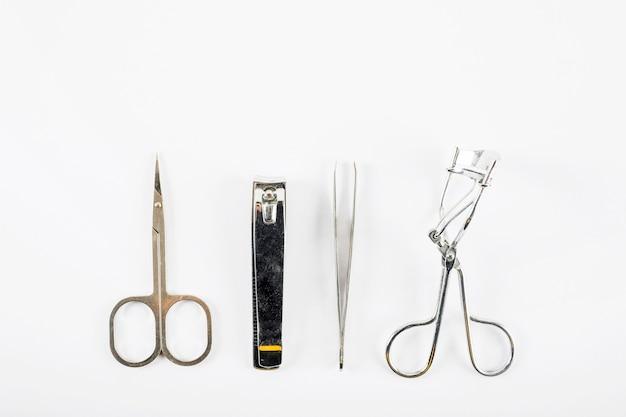 Visão aérea de tesoura; cortador de unha; pinça e cílios encrespador em fundo branco