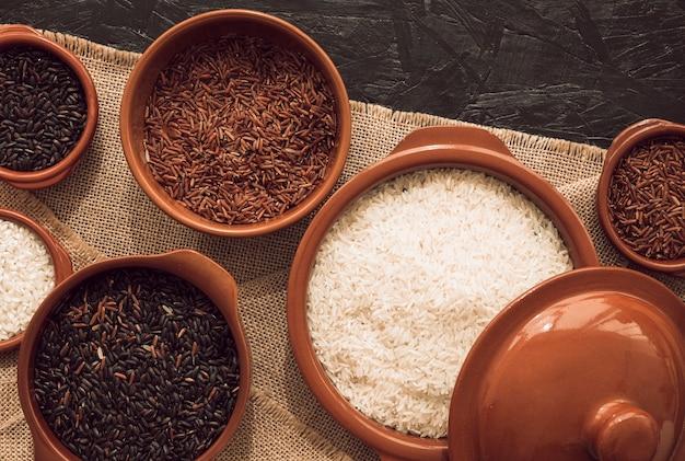 Visão aérea de tigelas de arroz crus na toalha de mesa de juta