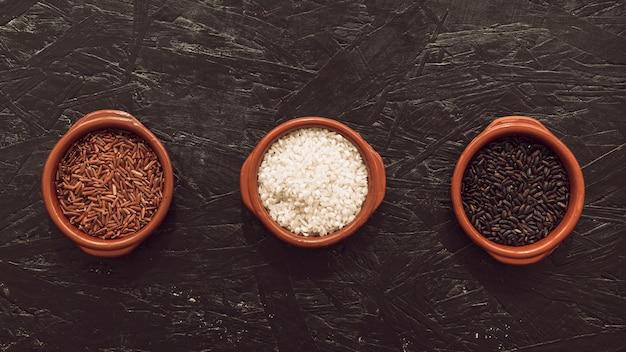 Visão aérea, de, três, orgânica, arroz, grão, tigela, ligado, áspero, textured, fundo