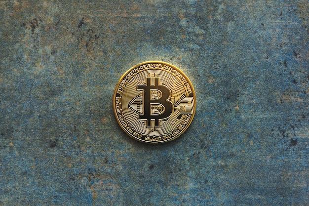 Visão aérea de um bitcoin dourado em um plano de fundo texturizado