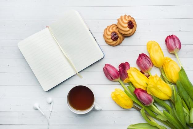 Visão aérea de um buquê de tulipas e notebook e uma xícara de café.