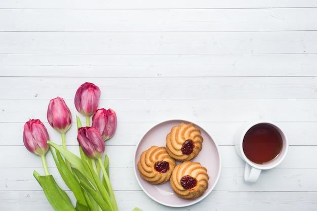 Visão aérea de um buquê de tulipas e uma xícara de café. copie o espaço. vista plana leiga