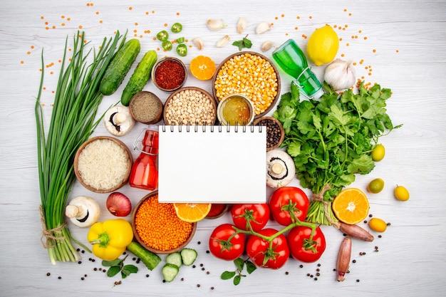 Visão aérea de um caderno espiral em legumes frescos, limão, grãos, milho, limão, óleo, caído, mel, garrafa, mel, fundo branco