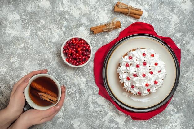 Visão aérea de um delicioso bolo cremoso decorado com frutas em uma toalha vermelha