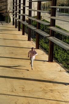 Visão aérea de um homem gordo correndo pela cidade vestido com roupas esportivas