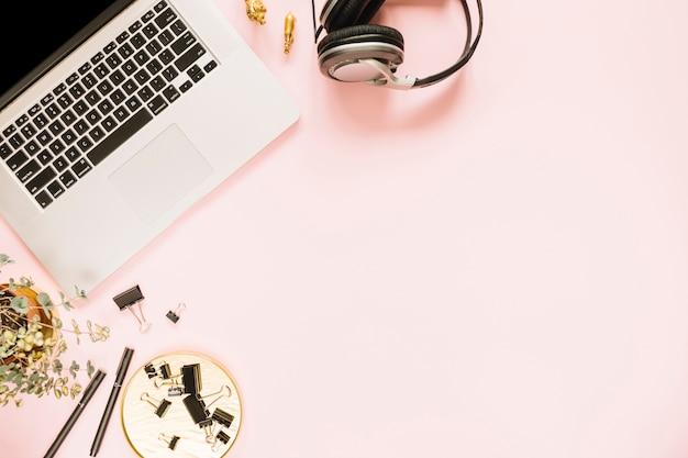 Visão aérea de um laptop aberto no pano de fundo rosa