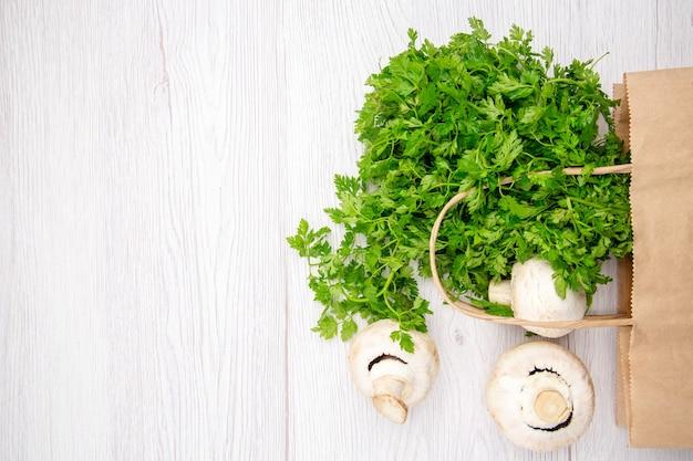 Visão aérea de um pacote de brócolis de cogumelos verdes frescos em uma cesta no fundo branco