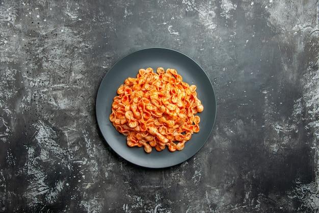 Visão aérea de uma deliciosa refeição de massa em uma placa preta para o jantar em fundo escuro