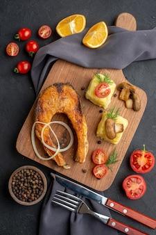 Visão aérea de uma deliciosa refeição de peixe frito com cogumelos, tomate, queijo na placa de madeira, rodelas de limão, pimenta em toalha de cor escura talheres na superfície preta