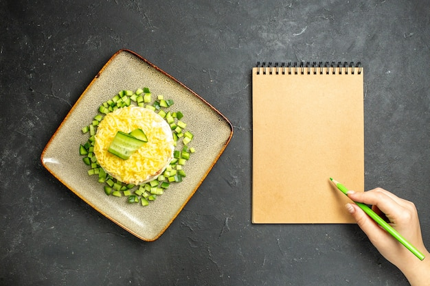 Visão aérea de uma mão escrevendo no caderno e uma deliciosa salada servida com pepino picado em fundo escuro