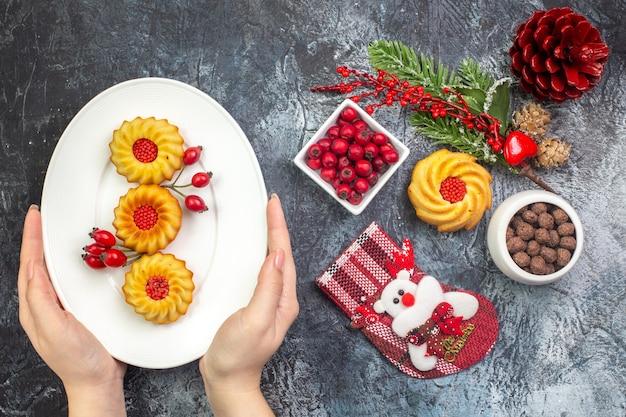 Visão aérea de uma mão segurando um prato branco com deliciosos biscoitos acessórios de decoração, meia de papai noel e cornell em uma tigela ramos de abeto na superfície escura