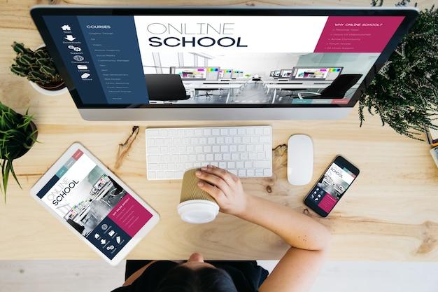 Visão aérea de uma mulher tomando café e dispositivos exibindo um projeto escolar on-line responsivo