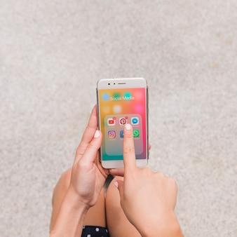 Visão aérea de uma pessoa apontando para o aplicativo de mídia social móvel