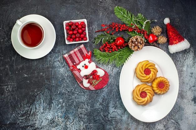 Visão aérea de uma xícara de chá com biscoitos deliciosos em um prato branco, chapéu de papai noel e chocolate em uma tigela na superfície escura