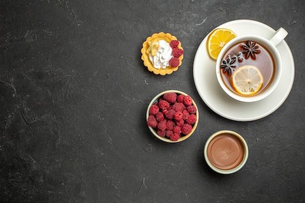 Visão aérea de uma xícara de chá preto com limão servido com mel de framboesa e chocolate em fundo escuro