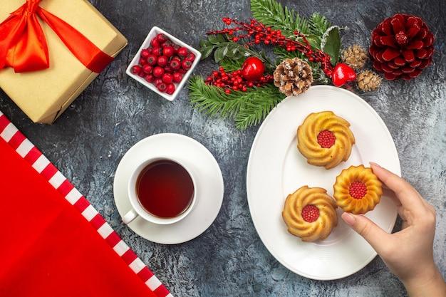 Visão aérea de uma xícara de chá preto, uma toalha vermelha e uma mão pegando biscoitos de um prato branco de presentes de acessórios de ano novo com fita vermelha na superfície escura