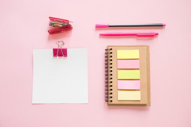 Visão aérea de vários artigos de papelaria no pano de fundo rosa