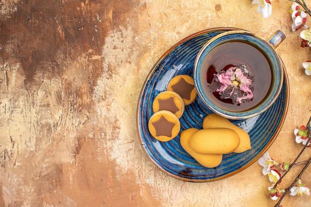 Visão aérea de vários biscoitos, uma xícara de chá e flores na mesa de cores misturadas