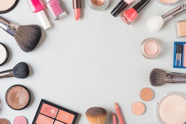 Visão aérea de vários produtos de maquiagem, formando a forma circular no fundo branco