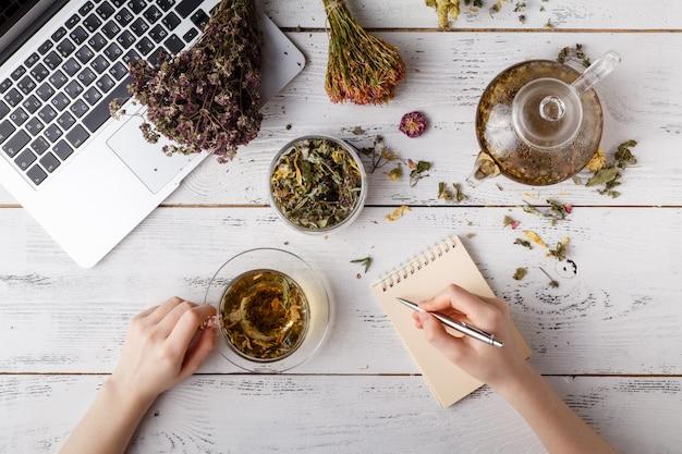 Visão aérea de vários tipos de chá. aromatizado com ervas sortidas, uma maçã, rosa com um bule e uma xícara de chá em uma mesa rústica