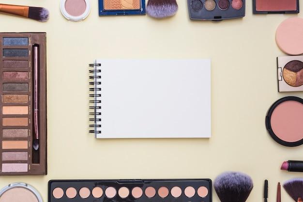 Visão aérea do bloco de notas espiral em branco cercado com produtos cosméticos