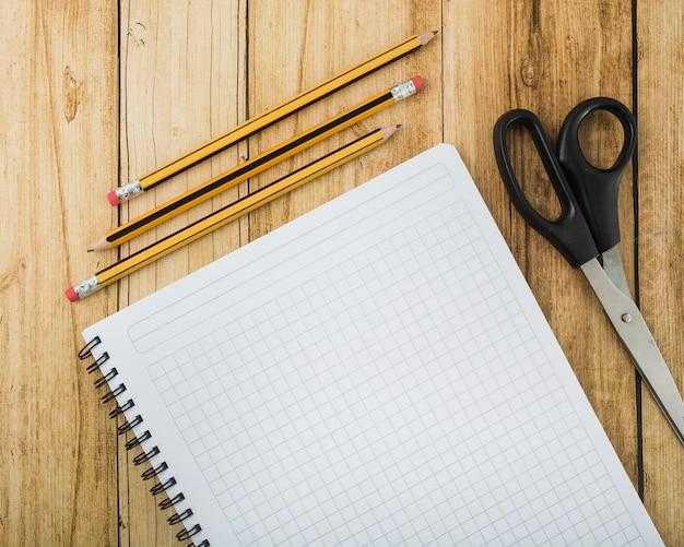 Visão aérea do bloco de notas; tesoura e lápis na prancha de madeira